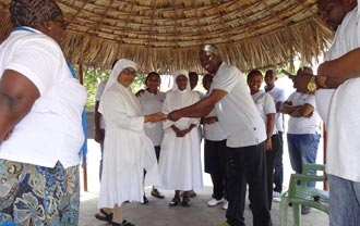 Sister Mary Jacintha of Liitle Sisters of the Poor in Tudor receive a check of Ksh.50,000.00 from the company and sister Jane and KEAL employees look on